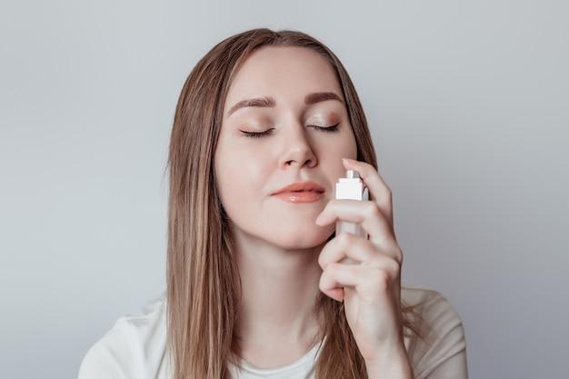 Perda do conceito de cheiro. jovem caucasiana cheirando perfume isolada