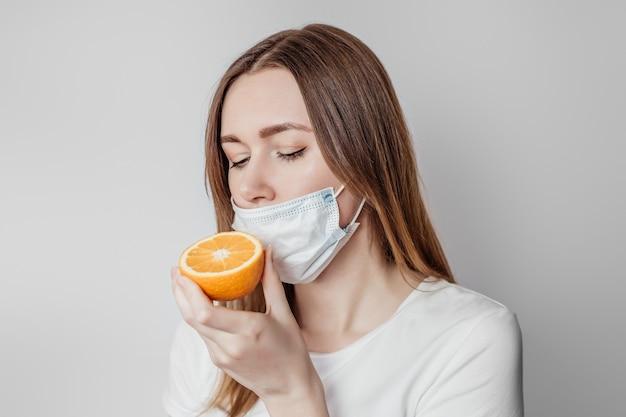 Perda do conceito de cheiro. jovem caucasiana com uma máscara médica cheirando uma laranja