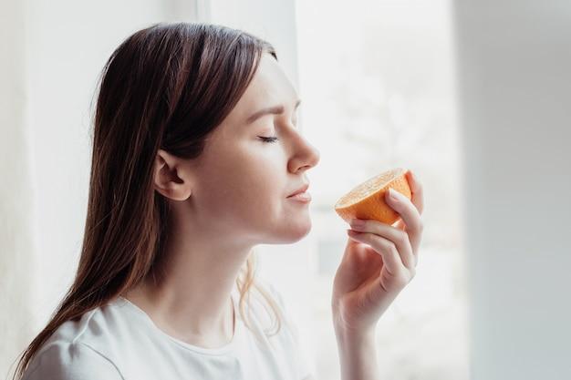 Perda do conceito de cheiro. mulher caucasiana em pé perto da janela cheirando uma laranja