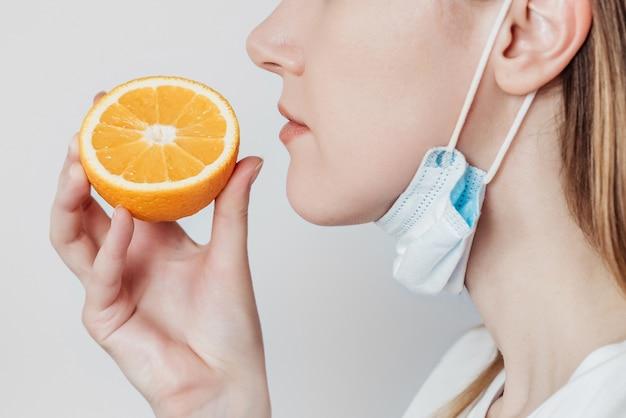 Perda do conceito de cheiro. mulher jovem caucasiana com uma máscara médica cheirando uma laranja. vista de perfil