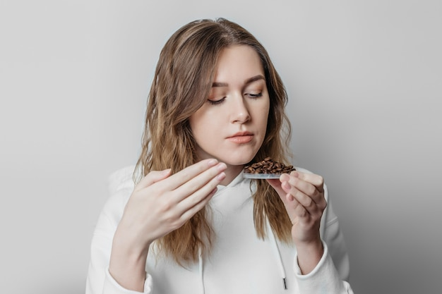 Perda do olfato feche o retrato de uma jovem caucasiana cheirando grãos de café isolados