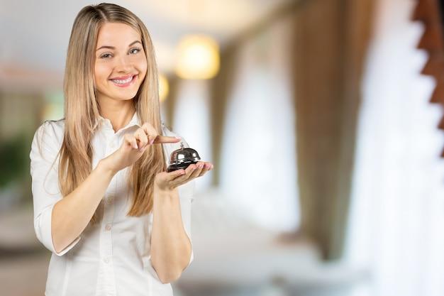 Perder as mulheres chamam a recepção do hotel na mesa de balcão com o dedo empurrar um sino