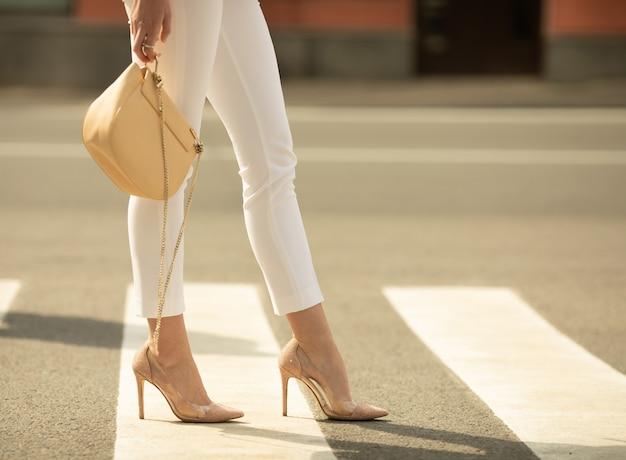 Perder as pernas da mulher andando na faixa de pedestres. a mulher está usando sapatos de salto alto. bolsa na mão da mulher.
