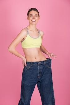 Perder peso e fazer dieta antes e depois do conceito. mulher slim fit mostrando resultados após fitness e exercícios, segurando velhas calças grandes sobre a cintura fina