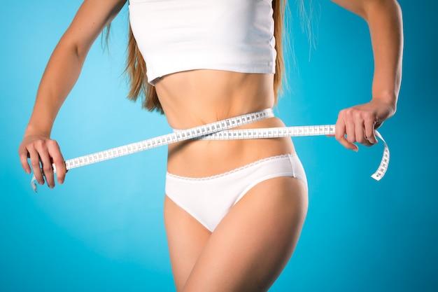 Perder peso, jovem mulher está medindo sua cintura