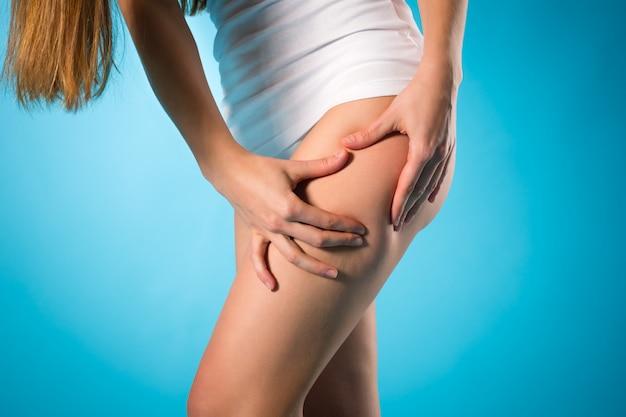 Perder peso, jovem mulher verificando a perna