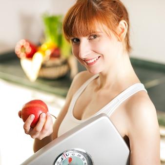 Perder peso - mulher com escala e apple