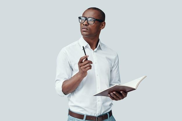 Perdido em pensamentos. africano jovem bonito olhando para longe em um fundo cinza