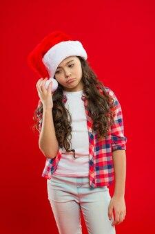 Perdido em pensamentos de natal. compras de natal. festa de ano novo. criança de papai noel. boas férias de inverno. uma pequena garota triste. presente para o natal. infância. menina com chapéu de papai noel vermelho.