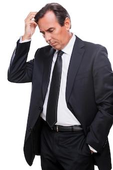 Perdido em pensamentos de negócios. homem maduro preocupado em trajes formais, segurando a mão no cabelo e olhando para longe em pé, isolado no fundo branco