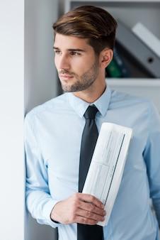 Perdido em pensamentos de negócios. jovem pensativo de camisa e gravata segurando o jornal