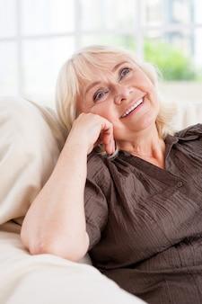 Perdido em pensamentos. mulher pensativa sênior segurando a mão no queixo e sorrindo enquanto está sentada em uma cadeira