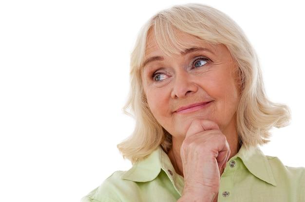 Perdido em pensamentos. mulher sênior pensativa segurando a mão no queixo e desviando o olhar enquanto fica de pé, isolado no fundo branco