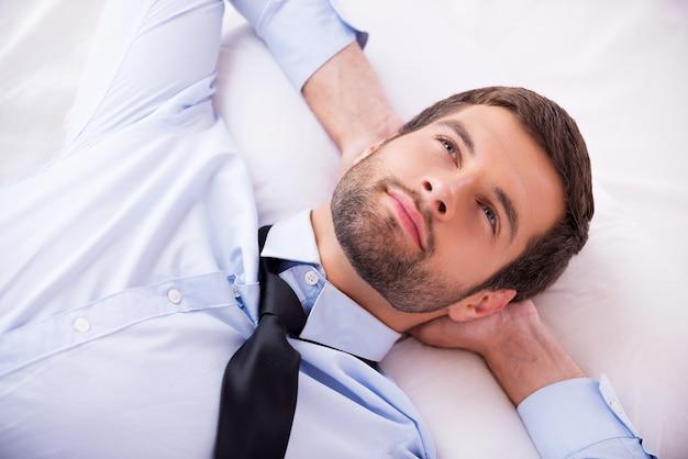 Perdido em pensamentos. vista superior de um jovem bonito de camisa e gravata, segurando as mãos atrás da cabeça e sorrindo enquanto está deitado na cama