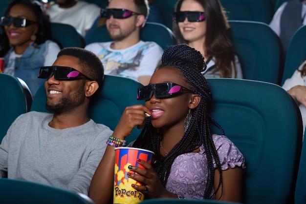 Perdido no mundo da ação. retrato de uma bela mulher africana tomando sua bebida enquanto assiste a um filme com o namorado no cinema