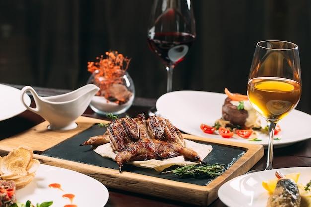 Perdiz grelhada, robalo, tártaro. pratos diferentes em cima da mesa no restaurante.