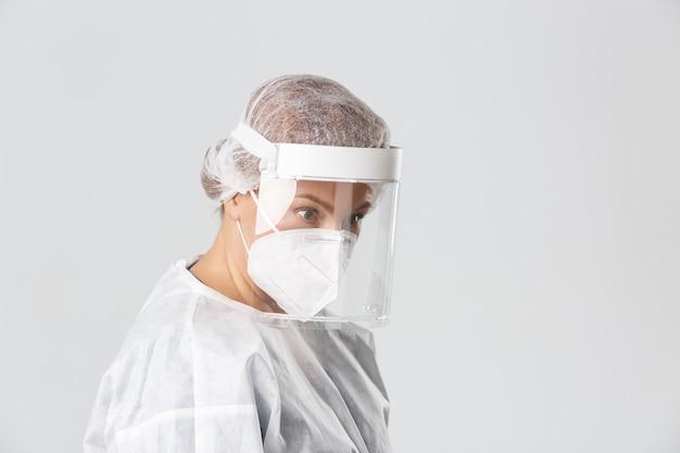 Perfil da médica surpresa em equipamento de proteção individual, olhando o ângulo inferior direito no paciente, plano de fundo cinza de pé.