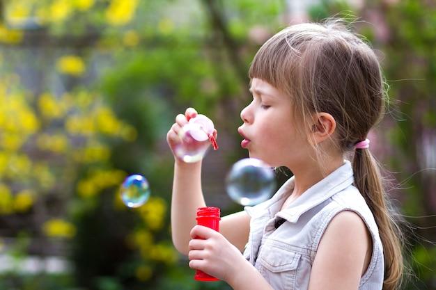 Perfil da menina loura pré-escolar consideravelmente pequena com a expressão séria engraçada que funde bolhas de sabão transparentes coloridas fora no verão verde borrado. alegria do conceito de infância descuidada.