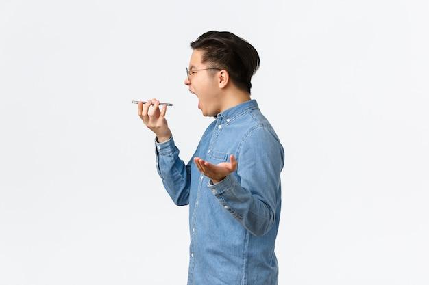 Perfil de cara asiático indignado e furioso perdendo a paciência, gritando frustrado, discutindo por telefone, gritando no alto-falante do telefone enquanto grava mensagem de voz com raiva, fundo branco