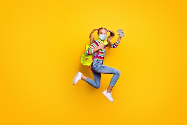 Perfil de corpo inteiro, vista lateral dela, ela é uma garota atraente e bonita pulando se divertindo usando máscara de gaze anti gripe infecção gripe