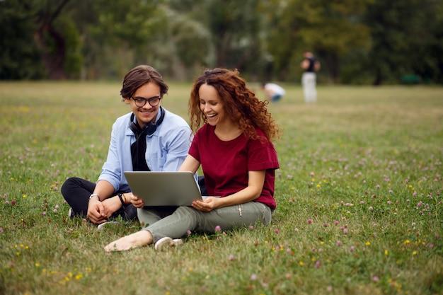 Perfil de dois colegas sorridentes, sentado em uma grama verde, olhando em um laptop no fundo urbano do parque.