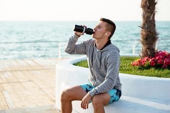 Perfil de esportista bonito no sportswear bebendo uma garrafa de água depois de treino