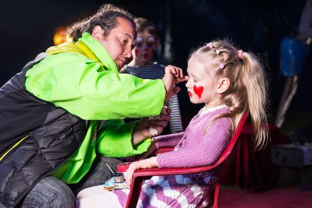 Perfil de garota loira sentada na cadeira tendo maquiagem de palhaço aplicada no rosto pelo homem
