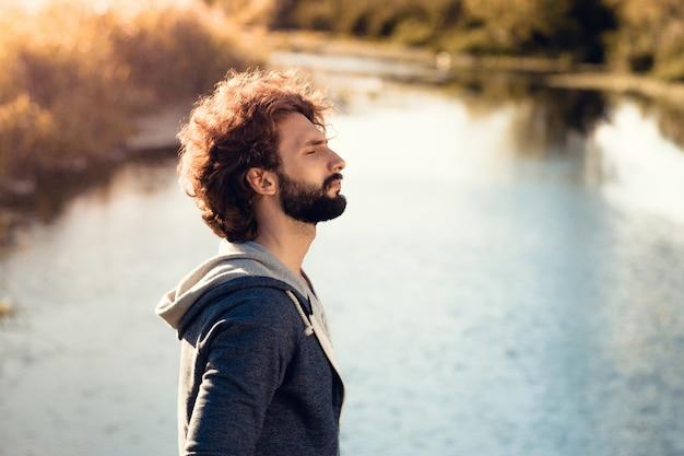 Perfil de homem barbudo no rio