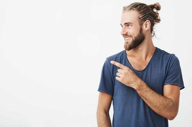 Perfil de homem bonito alegre com penteado elegante e barba sorrindo brilhantemente e apontando para copyspace