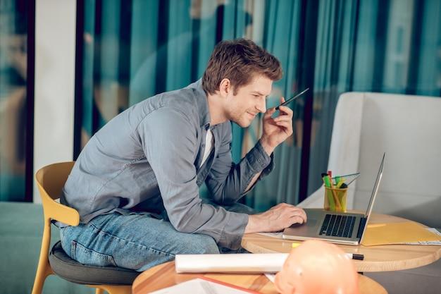 Perfil de homem feliz trabalhando em um laptop