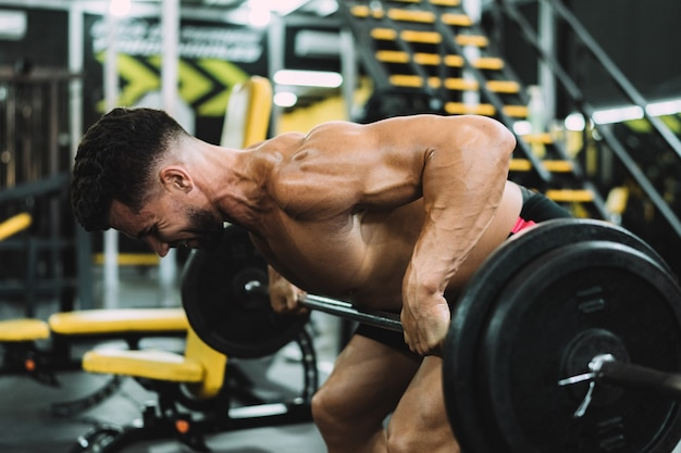 Perfil de homem forte levantando peso com a barra em uma academia