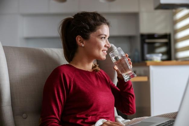 Perfil de jovem morena sentada em casa e bebendo água.