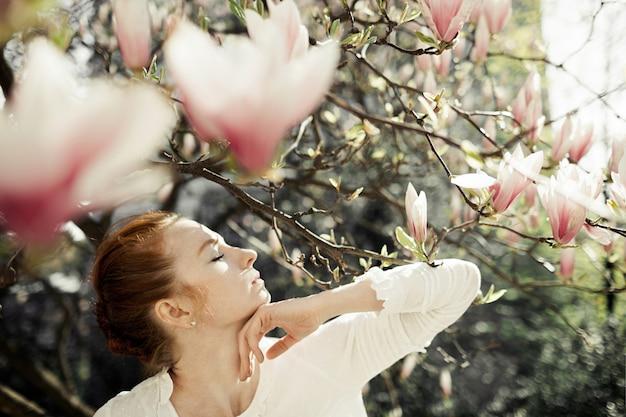Perfil de menina bonita com flores de magnólia