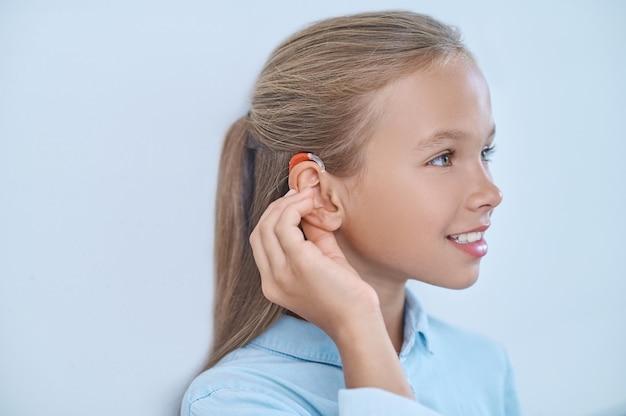 Perfil de menina tocando ouvido com aparelho auditivo