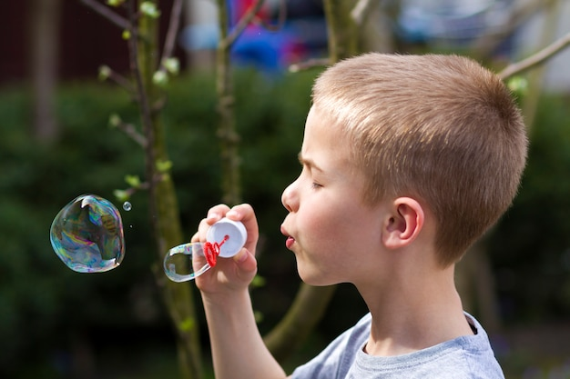 Perfil de menino loiro pequeno bonito bonito criança com expressão séria engraçada soprando bolhas de sabão transparentes coloridas ao ar livre no verão verde turva. alegria do conceito de infância descuidada.