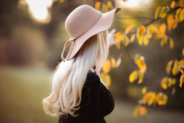 Perfil de mulher atraente, com longos cabelos loiros no chapéu rosa de outono.