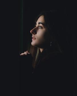 Perfil de mulher bonita com medo olhando no escuro. rosto triste adolescente deprimido olhando através de uma janela em uma casa abandonada