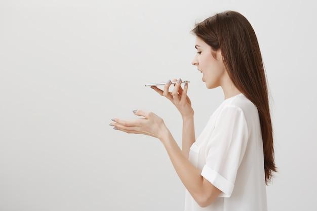 Perfil de mulher falando no viva-voz ou grava mensagem de voz com o celular