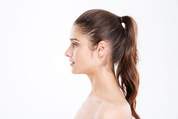 Perfil de mulher jovem e atraente com rabo de cavalo sobre uma parede branca