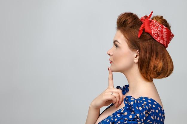 Perfil de mulher jovem e atraente ruiva com penteado vintage usando vestido azul e lenço na cabeça vermelho tocando o queixo, pensando em algo, posando para uma parede em branco com espaço de cópia para o seu texto
