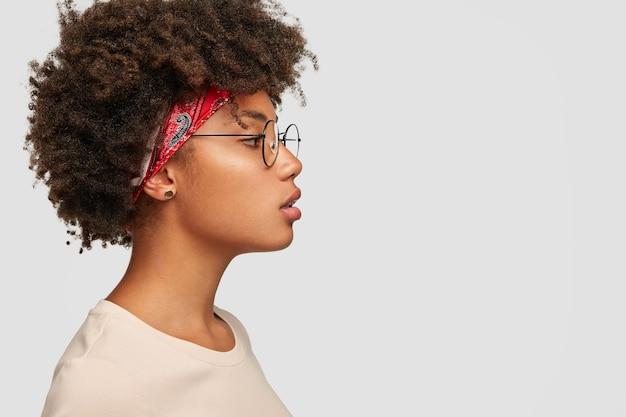 Perfil de mulher séria com pele pura e saudável, com penteado espesso