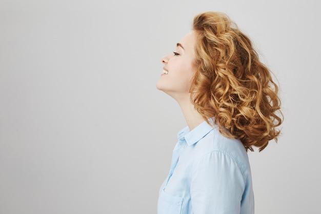 Perfil de mulher sorridente e despreocupada com cabelo curto e encaracolado
