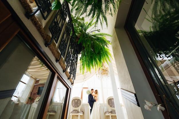 Perfil de recém-casados nos braços um do outro no salão do restaurante com samambaias no interior