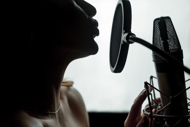 Perfil de silhueta escura de uma jovem mulher com ombros nus, cantando no microfone