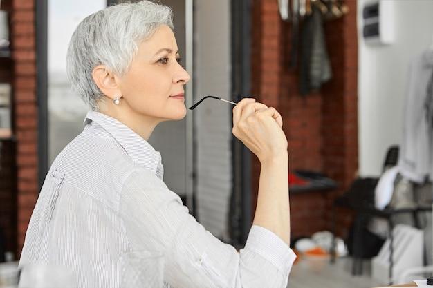 Perfil de uma bela escritora de meia-idade concentrada com um corte de cabelo elegante, sentada no escritório em casa com expressão facial pensativa, segurando óculos, tendo um sorriso inspirado, escrevendo um livro