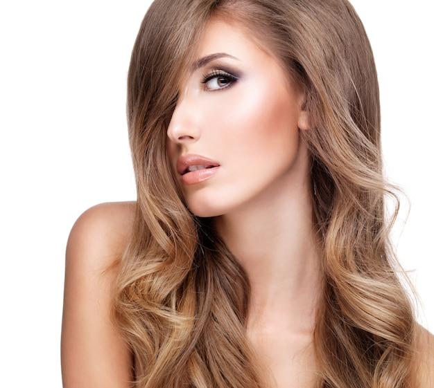 Perfil de uma bela jovem com cabelos longos ondulados e maquiagem