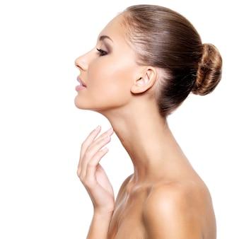 Perfil de uma bela jovem com pele limpa e fresca tocando suavemente seu pescoço, isolado no branco