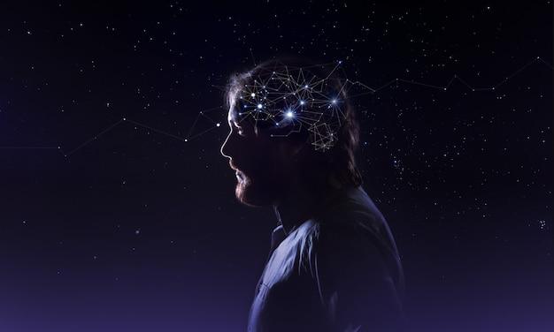 Perfil de uma cabeça de homem barbudo com neurônios de símbolo no cérebro. pensando como estrelas, o cosmos dentro do céu noturno humano de fundo
