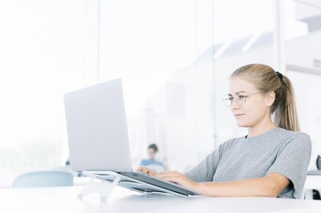 Perfil de uma garota loira trabalhando com um laptop em um coworking e pessoas ao redor