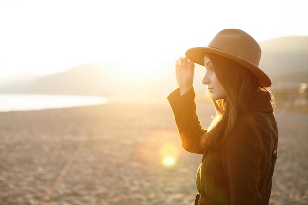 Perfil de uma jovem encantadora de chapéu e casaco passando uma noite quente ao ar livre